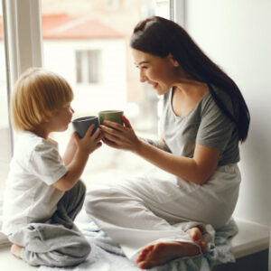 mother-little-son-sitting-windowsill-with-tea_1157-29388